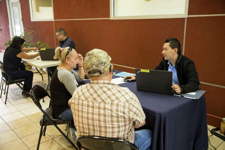 Mario Cruz helps Miriam Suarez and Raul Suarez enroll at the CentroMed Noemi Galvan Eling Clinic in San Antonio on November 10, 2016. Photo: Carolyn Van Houten /San Antonio Express-News / 2016 San Antonio Express-News