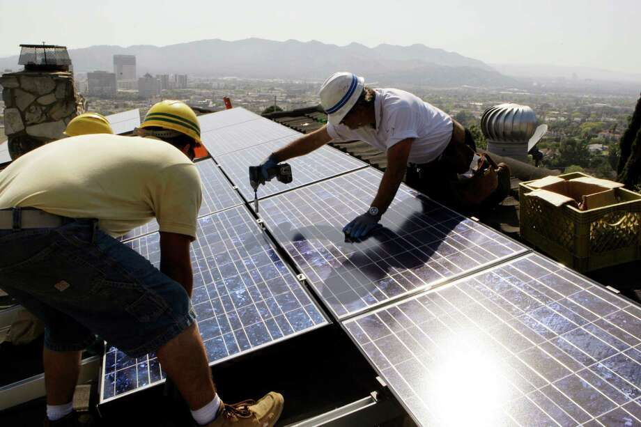 FILE - In this March 23, 2010, file photo, installers from California Green Design install solar electrical panels on the roof of a home in Glendale, Calif. The Obama administration is boosting the development of solar and wind energy on public lands. A final rule announced by the Interior Department on Thursday, Nov. 10, 2016, would create a new leasing program on public lands and encourage development in areas where it would have fewer effects on the environment.  (AP Photo/Reed Saxon, File) ORG XMIT: WX103 Photo: Reed Saxon / Copyright 2016 The Associated Press. All rights reserved. This m