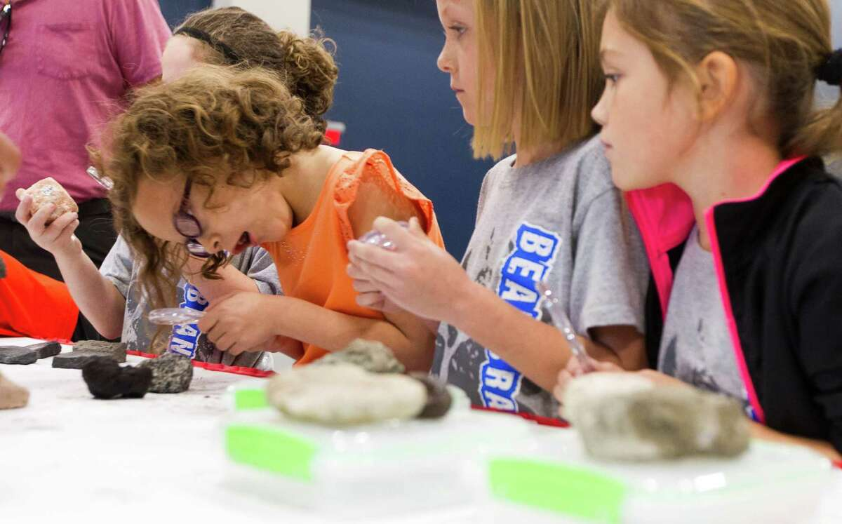 A student from Bear Branch Junior High School examines a rock sample as part of a geology exhibit during the annual Children's Festival at the Cynthia Woods Mitchell Pavilion Thursday, Nov. 10, 2016, in The Woodlands.