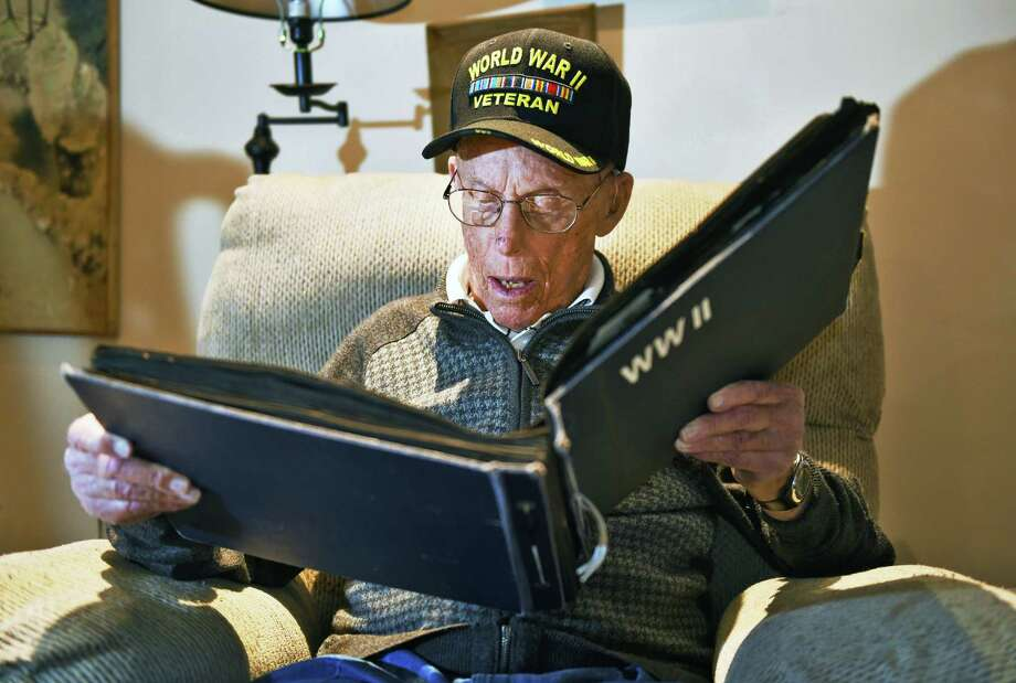 Charlie Kapner, 99, looks over photographs he took as a Tech Sgt. and radio operator in the 87th Division during WWII at his apartment Wednesday Nov. 9, 2016 in Albany, NY.  (John Carl D'Annibale / Times Union) Photo: John Carl D'Annibale / 20038493A