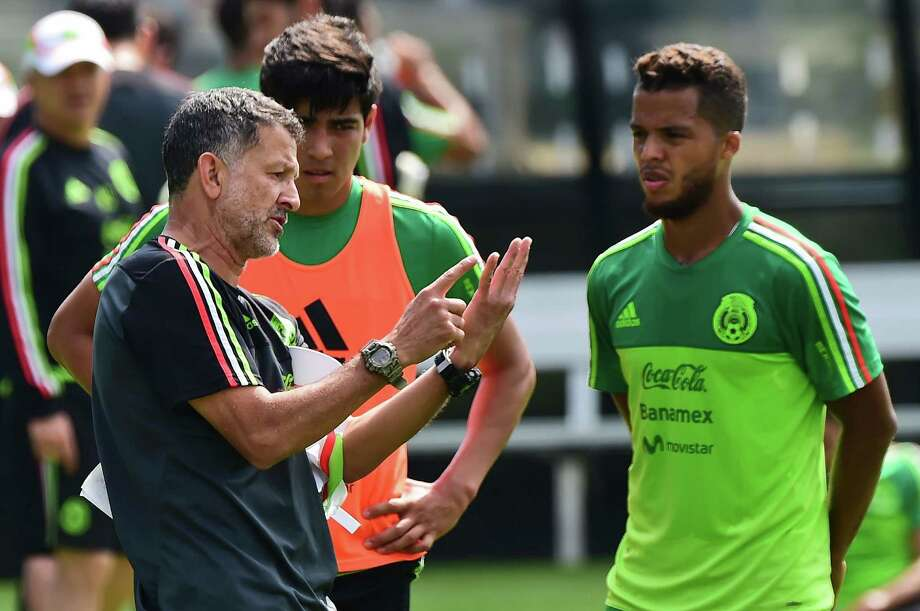 The coach of Mexico's national football team, Colombian Juan Carlos Osorio (L) speaks with Giovani dos Santos (R) during a training session in Mexico City on October 4, 2016 ahead of the upcoming international friendly matches against New Zealand and Panama. / AFP PHOTO / Ronaldo SCHEMIDTRONALDO SCHEMIDT/AFP/Getty Images Photo: RONALDO SCHEMIDT / AFP or licensors