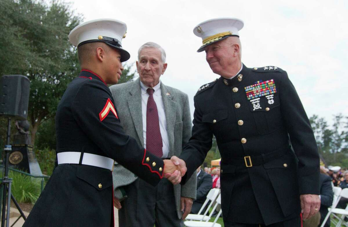 Retired Lt. General Steve Hummer, right, shakes hands with Private First Class Adrian Zaldivar, of Humble, as Tom Early looks on during a celebration in honor of the U.S. Marine Corps' 241st birthday at Town Green Park Thursday, Nov. 10, 2016, in The Woodlands.