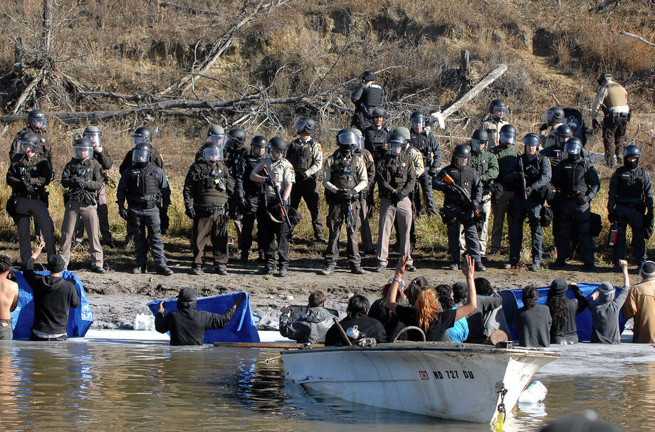 Dakota Access Pipeline protesters stand waist deep in the Cantapeta Creek, northeast of the Oceti Sakowin Camp, near Cannon Ball, N.D., Wednesday, Nov. 2, 2016. Officers in riot gear clashed again Wednesday with protesters near the Dakota Access pipeline, hitting dozens with pepper spray as they waded through waist-deep water in an attempt to reach property owned by the pipeline's developer. (Mike Mccleary/The Bismarck Tribune via AP) Photo: Mike Mccleary, MBO / The Bismarck Tribune