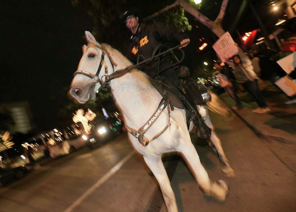 A mounted police holds onto his horse while protesters take to the streets in downtown Houston to share their displeasure with Donald Trump being the president elect on Thursday, Nov. 10, 2016.