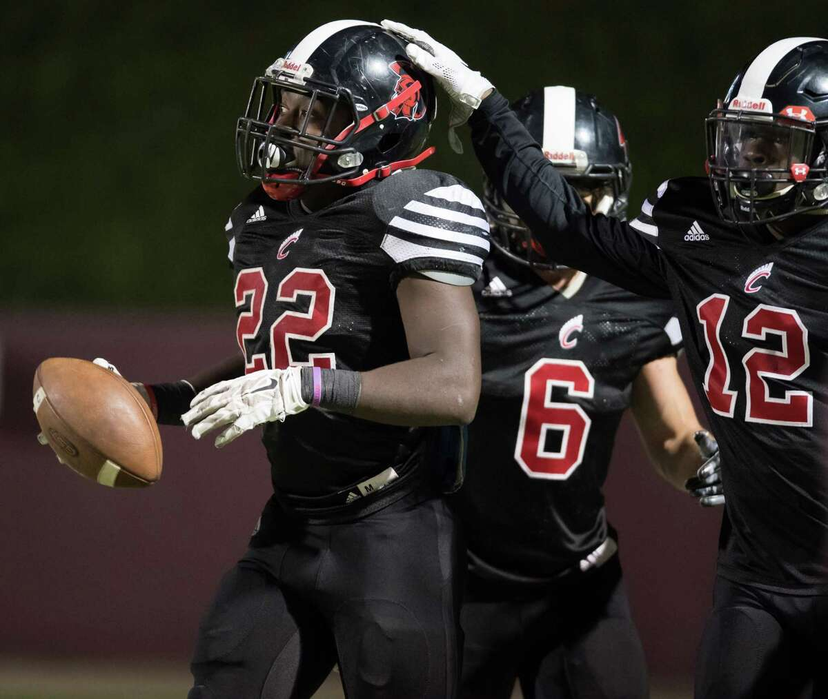 Dvontae McKinney (12) of the Coldspring Trojans congratulates Don Taylor (22) after one of his four touchdowns against the La Marque Cougars in a high school football Class 3A Division 1 Bi-District Playoff Game on Thursday, November 10, 2016 at Abshier Stadium in Deer Park Texas.