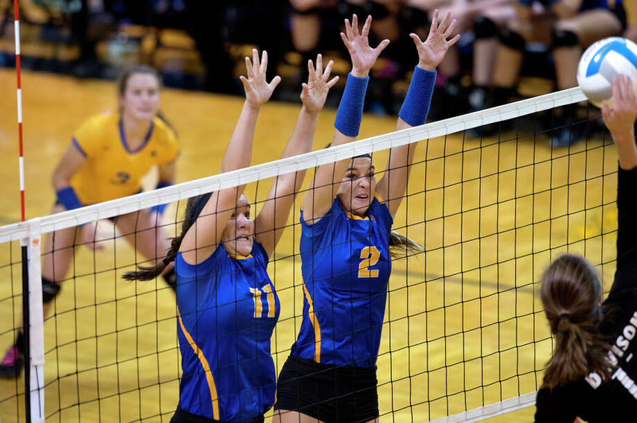 BRITTNEY LOHMILLER | blohmiller@mdn.net Midland High's Alexandria McMath, left, and Peyton Gerstacker jump to block a spike from Davison High's Maria Vukaj in the third set of the Class A regional volleyball championship match Thursday evening at Mount Pleasant High School. The Chemics defeated Davison 21-25, 25-18, 25-21, 20-25, 15-13. Midland will play in the MHSAA quarterfinal match at H.H. Dow High School Nov. 15 at 6 p.m.