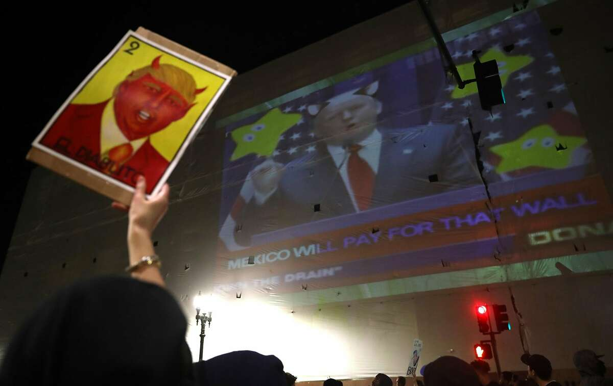Donald Trump protest marchers pass Trump video being projected on the old Sears building on Telegarph in Oakland, Calif., on Thursday, November 10, 2016.