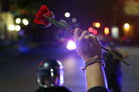 Max Gee holds a rose as Oakland Police stop a Donald Trump protest march on 14th Street in Oakland, Calif., on Thursday, November 10, 2016.