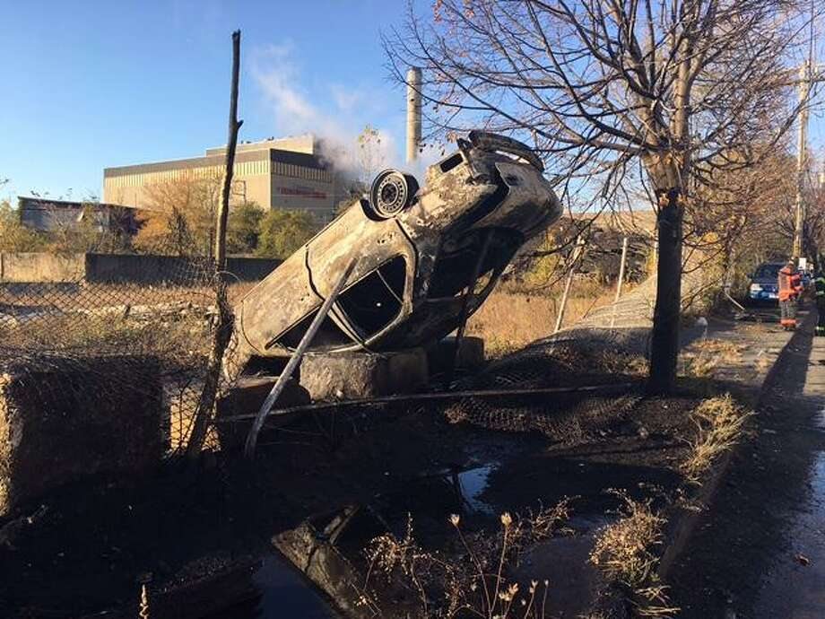 """A woman was ejected from her car after losing control of the vehicle on Wordin Avenue in Bridgeport on Friday, Nov. 11, 2016. The woman was ejected from the vehicle after it rolled over and struck a concrete barriers and a fence. Officer Brian Pisanelli said a fisherman, who was nearby, saw the woman walking back to the car, but managed to """"drag her to safety"""" seconds beforethe car it exploded. Photo: Jim Shay /Hearst Connecticut Media"""