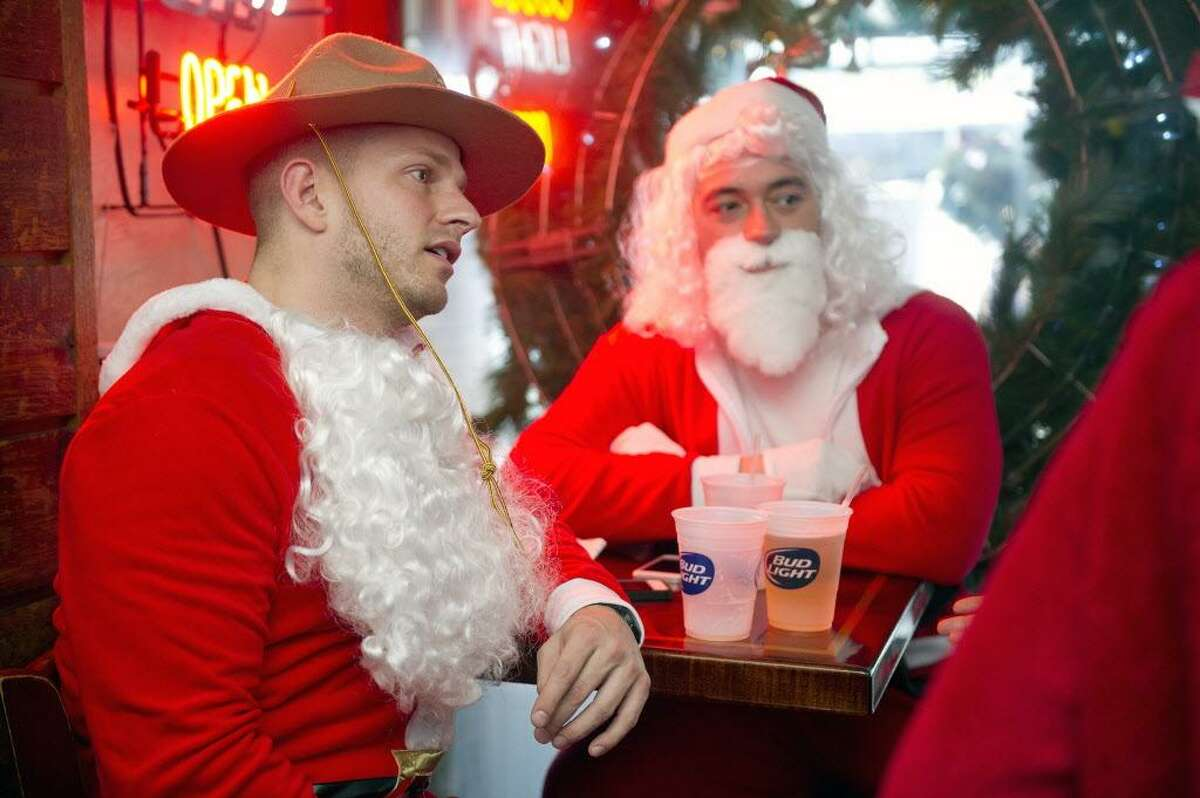 FILE - Brady Simpson, left, and Alex Ferro, right, both dressed as Santa, relax at Murphy's during Stamford SantaCon on Saturday, December 6, 2014.