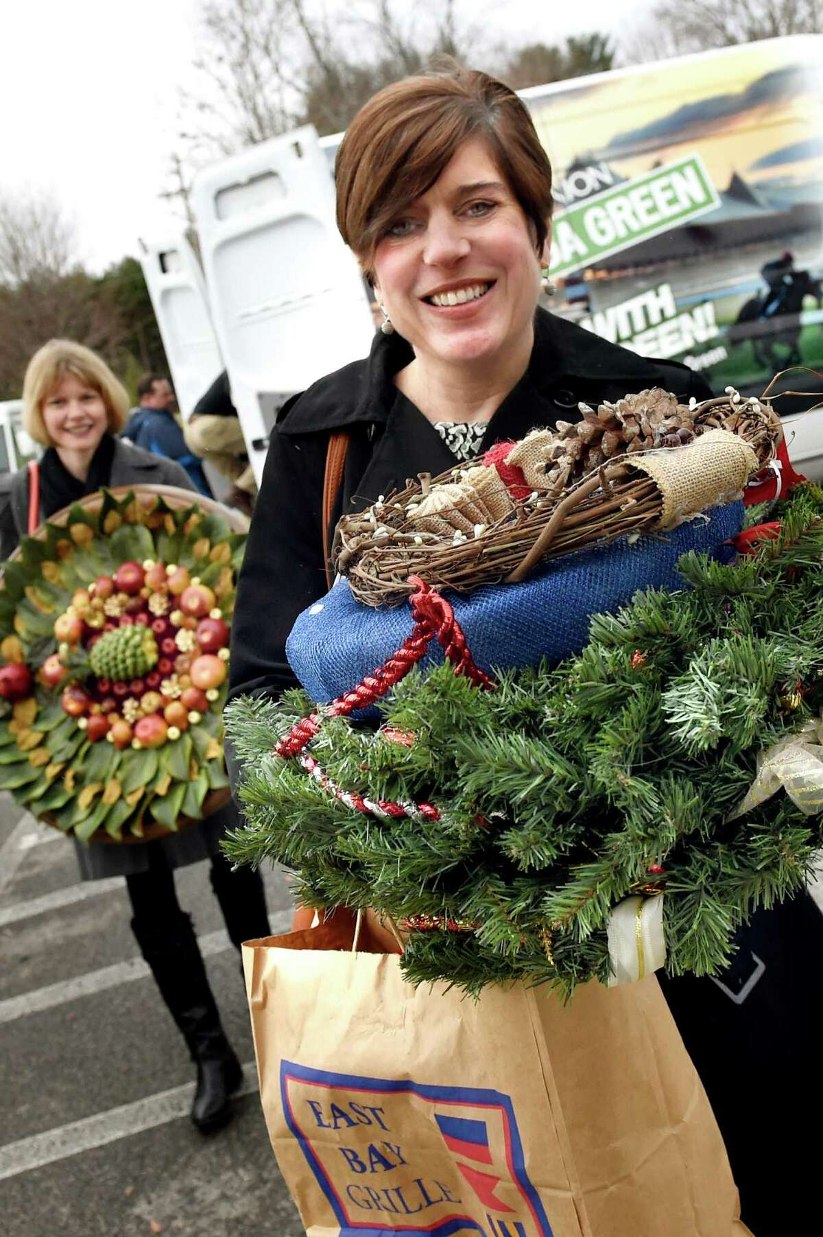 Times Union employees Jennifer Gish, left, and Tracy Ormsbee help deliver wreaths from the Times Union's Circles of Caring contest on Tuesday, Dec. 15, 2015, at Omni Senior Living of Guilderland in Guilderland, N.Y. (Cindy Schultz / Times Union)