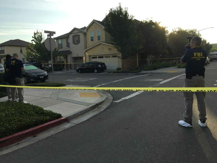 Crime-scene tape surrounds the area near a home where FBI agents probe a triple slaying in Oakland.