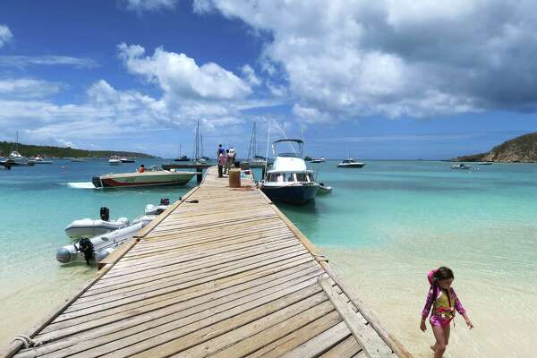 A child wades through the water along the pier at Road Bay in Sandy Ground on the Caribbean island of Anguilla. The pier is popular with visitors who take shuttle boats out to nearby Sandy Island for lunch and a day of snorkeling.