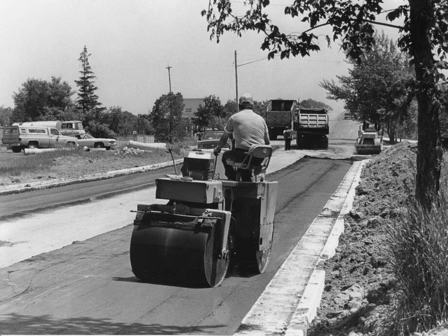 Employees of Saginaw Asphalt and Paving co. work on the new road surface on East Ashman. The road is being regraded and resurfaced from Waldo to Rockwell. June 1982 Photo: Daily News File Photo