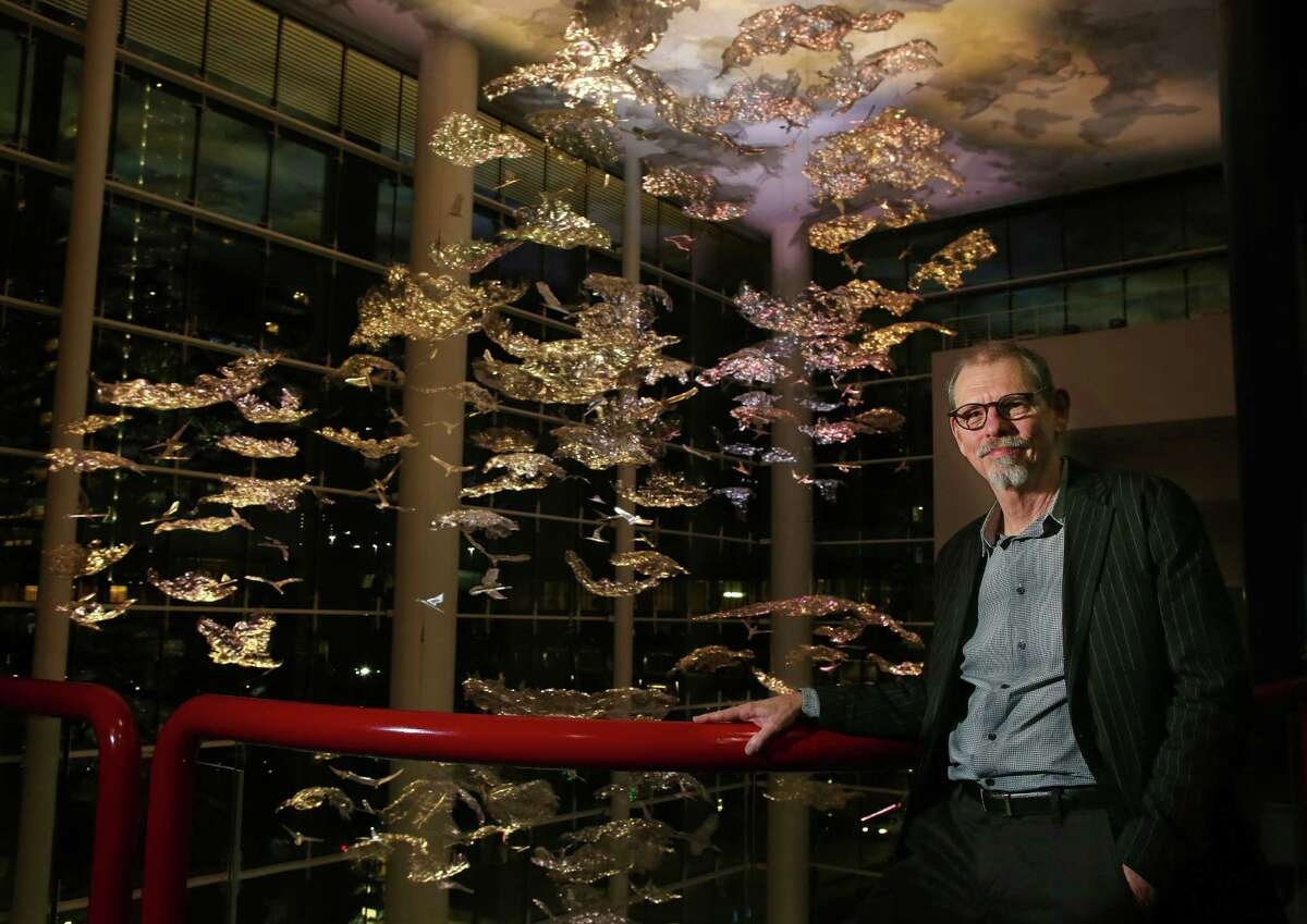 """Artist Ed Wilson stands by his new sculpture, """"Soaring in the Clouds,"""" inside the new grand lobby of the George R. Brown Convention Center in downtown Houston, Thursday, Nov. 10, 2016. The sculpture is made of many small pieces suspended from the almost 100-foot-high ceiling and lit by constantly changing colors. (Mark Mulligan/Houston Chronicle via AP)"""