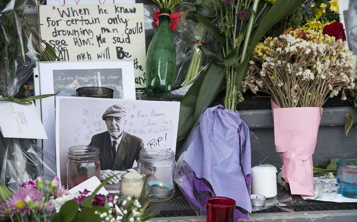 """A makeshift shrine is seen in front of the home of legendary singer and poet Leonard Cohen Friday, Nov. 11, 2016 in Montreal. Cohen, the baritone-voiced Canadian singer-songwriter who seamlessly blended spirituality and sexuality in songs like """"Hallelujah,"""" ''Suzanne"""" and """"Bird on a Wire,"""" has died at age 82, his son said. (Paul Chiasson/The Canadian Press via AP)"""