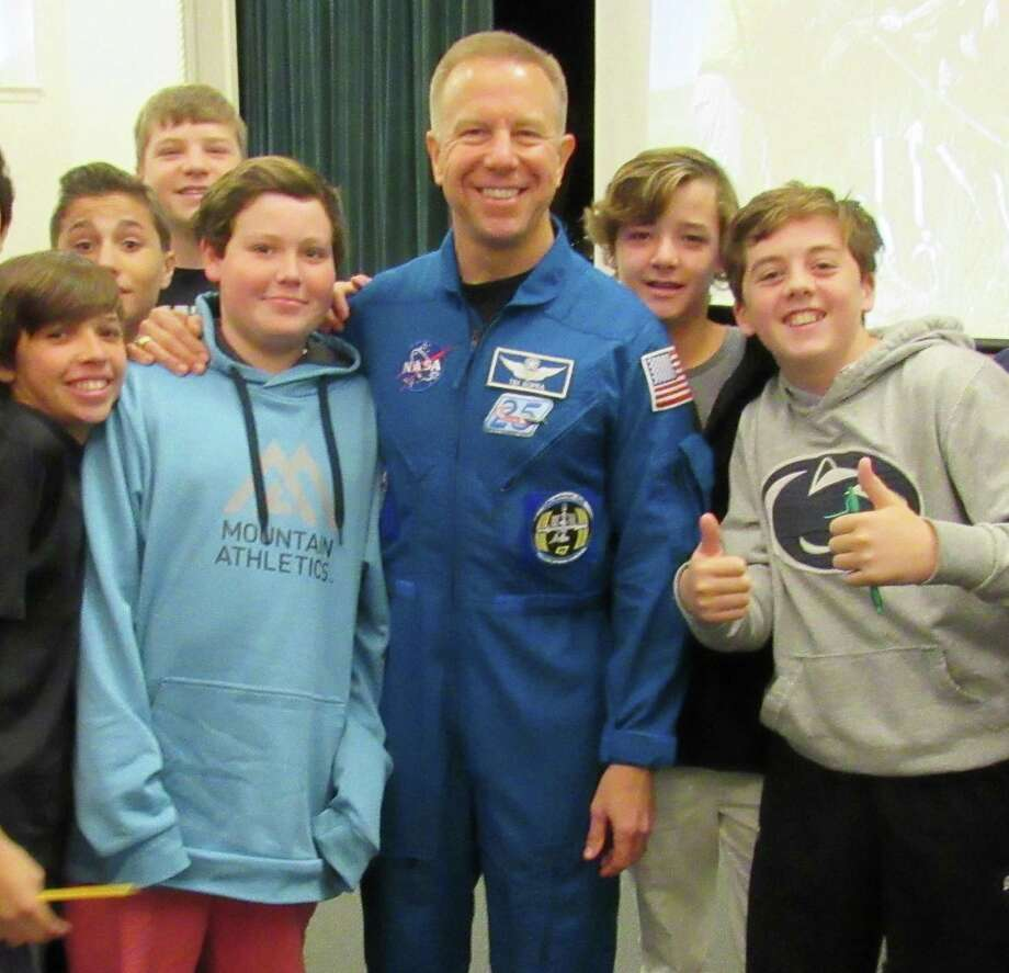 Tim Kopra, NASA Astronaut and former commander of the International Space Station, spoke to Middlesex Middle School students on Oct. 28 in Darien. He shared his experiences in space, including how astronauts sleep, exercise and spacewalk during their missions on the space shuttle. From left are Hunter Yarish, Tate Olsen, Myron Czebiniak, Jack Jachino, Kopra, Jack Simms and Charlie Pegler. Photo: Contributed Photo