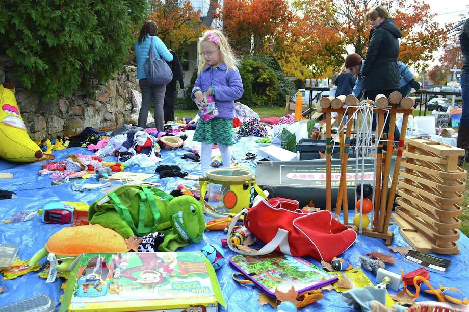 Alexandra Knowles, 4, of New Canaan, looks at some merchandise at the Junior League of Stamford-Norwalk's fall tag sale, Sunday in Darien. Photo: Jarret Liotta / For Hearst Connecticut Media / Darien News Freelance