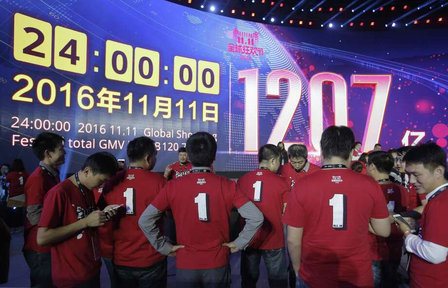 "Attendants stand in front of a giant screen showing a total sales transacted of e-commerce giant Alibaba, on the ""Singles' Day"" global online shopping festival in Shenzhen, southern China's Guangdong province Saturday, Nov. 12, 2016. In a bright spot for China's cooling economy, online shoppers spent billions of dollars Friday on ""Singles Day,"" a quirky holiday that has grown into the world's busiest day for e-commerce. Photo: Kin Cheung / Associated Press / Copyright 2016 The Associated Press. All rights reserved."