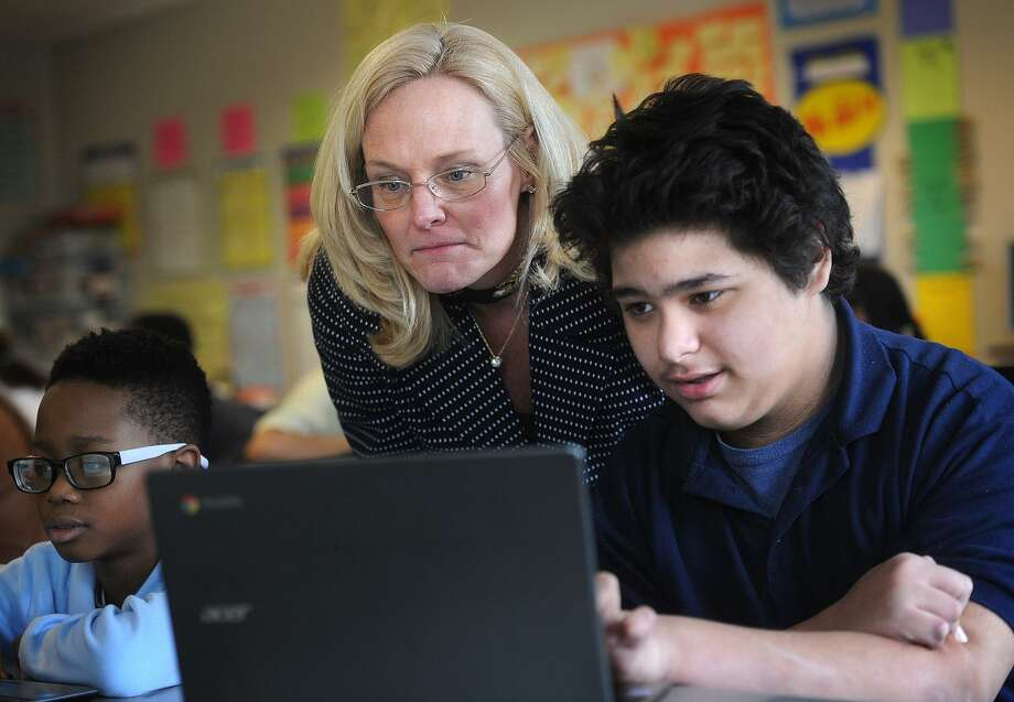 Sixth grader teacher Kathy Cunningham and student Jayvan Marrero, 12, review the format of the new common core standardized test, which will be taken online, at Jettie Tisdale School in Bridgeport in 2015. Photo: Brian A. Pounds / Hearst Connecticut Media / Connecticut Post