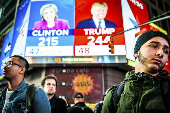 """FILE-- People watch election results at Times Square in New York, Nov. 9, 2016.  Clinton has followed Al Gore as the second Democratic presidential candidate in modern history to be defeated by a Republican who earned fewer votes, in his case by George W. Bush. Even President-elect Donald Trump, who won the electoral vote but lost the popular vote, called the system """"a disaster for a democracy"""" in 2012.  (George Etheredge/The New York Times)"""