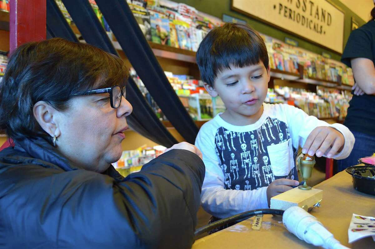 Sally Cascella of Monroe watches Alexander Weil of Fairfield work on his car at the Westport Barnes & Noble's second annual Mini Maker Faire, Saturday, Nov. 5.