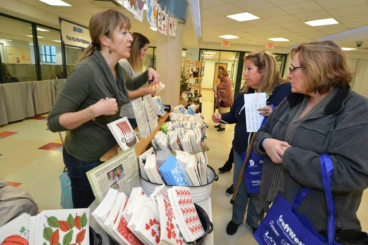 Marie Caspole from Fairfield and Jan Grey from Bridgeport shop with Amy and Lynda Baldauf and the family business Three Bluebirds Swedish Dishcloths booth from Old Greenwich during CraftWestport on Sunday November 6, 2016 at Staples High School in Westport, Conn.