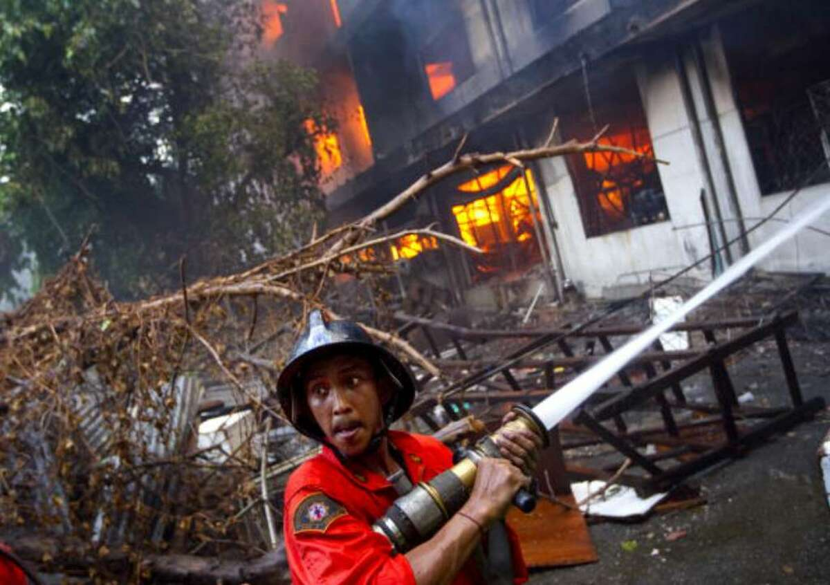 BANGKOK, THAILAND - MAY 18: Firefighters work to control a blaze set by Thai anti-government red shirt protesters on May 18, 2010 in Bangkok, Thailand. Protesters have clashed with military forces for five consecutive day in Bangkok after the government launched an operation to disperse anti-government protesters who have closed parts of the city for more than two months. Despite calls from the United Nations for both sides to begin talks, anti-government protesters in Bangkok have defied orders to leave their fortified camp, with 37 people having died and more than 260 injured since the military began its crackdown. (Photo by Paula Bronstein/Getty Images)
