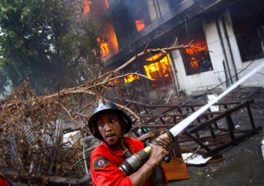 BANGKOK, THAILAND - MAY 18:  Firefighters work to control a blaze set by Thai anti-government red shirt protesters on May 18, 2010 in Bangkok, Thailand. Protesters have clashed with military forces for five consecutive day in Bangkok after the government launched an operation to disperse anti-government protesters who have closed parts of the city for more than two months. Despite calls from the United Nations for both sides to begin talks, anti-government protesters in Bangkok have defied orders to leave their fortified camp, with 37 people having died and more than 260 injured since the military began its crackdown. (Photo by Paula Bronstein/Getty Images) Photo: Paula Bronstein, Getty Images / 2010 Getty Images