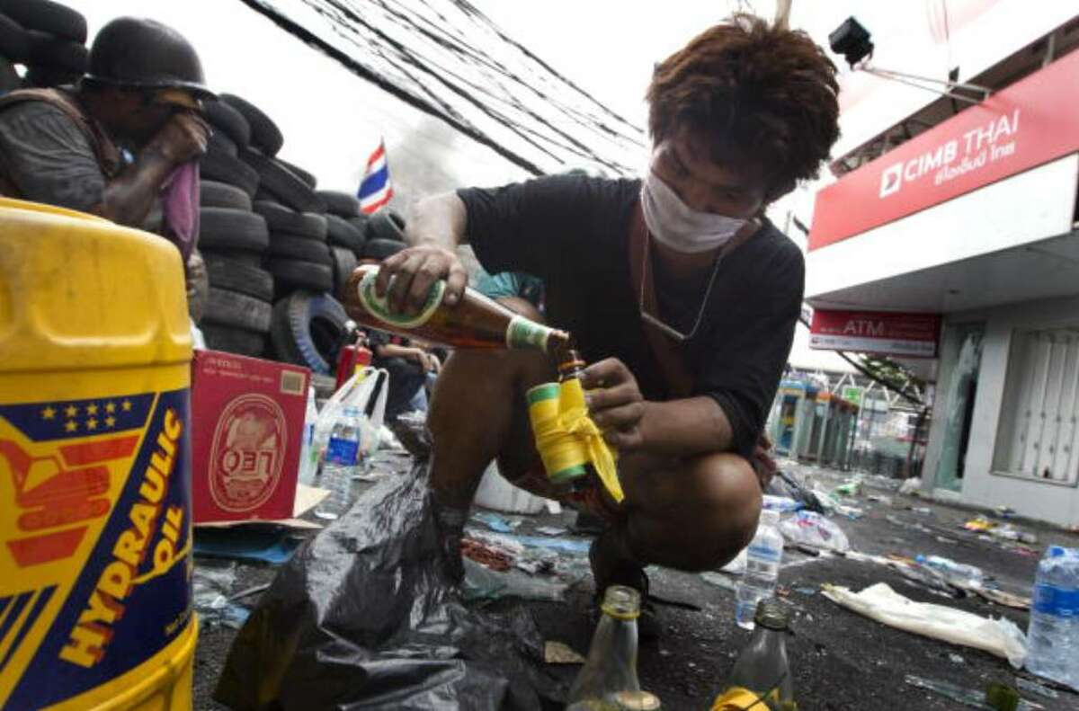 BANGKOK, THAILAND - MAY 18: A Thai anti-government red shirt protester fills a molotov cocktail on May 18, 2010 in Bangkok, Thailand. Protesters have clashed with military forces for five consecutive day in Bangkok after the government launched an operation to disperse anti-government protesters who have closed parts of the city for more than two months. Despite calls from the United Nations for both sides to begin talks, anti-government protesters in Bangkok have defied orders to leave their fortified camp, with 37 people having died and more than 260 injured since the military began its crackdown. (Photo by Paula Bronstein/Getty Images)