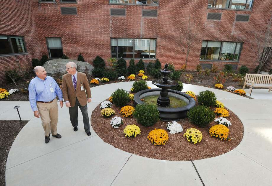At left, Scott Neff, development director at Nathaniel Witherell, speaks with Allen Brown, Nathaniel Witherell's executive director, as the pair stroll past the fountain that is part of the new enclosed garden in a courtyard at the Nathaniel Witherell nursing home in Greenwich, Conn., Thursday, Nov. 10, 2016. Photo: Bob Luckey Jr. / Hearst Connecticut Media / Greenwich Time