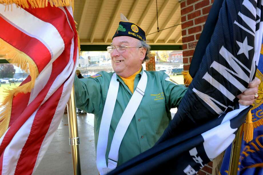 "John ""Jack"" Finn, a member of the color guard from American Legion Post 16 works to hang onto to flags in a strong wind during the Veterans Day ceremony in Shelton, Conn. Nov. 11, 2016. Photo: Ned Gerard / Hearst Connecticut Media / Connecticut Post"