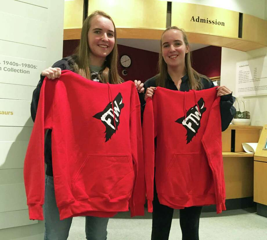 """From left: Carys and Claire Hacker, GHS students and members of the GHS Outreach Club, show off some sweatshirts they got at Thursday's """"Stress, Success and Teenage Setbacks Part II: Let's Talk Mental Health"""" at the Bruce Museum. The teens heard peers and experts talk about stress and its effects on youth. Photo: Peregrine Frissell"""