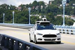 FILE - In this Thursday, Aug. 18, 2016, file photo, Uber employees test a self-driving Ford Fusion hybrid car, in Pittsburgh. After taking millions of factory jobs, robots could be coming for a new class of worker: people who drive for a living. (AP Photo/Jared Wickerham, File)