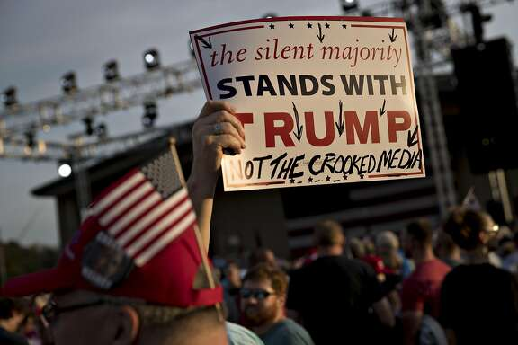 An attendee holds a campaign sign towards the media ahead of a campaign rally with Donald Trump, 2016 Republican presidential nominee, in Selma, North Carolina, U.S., on Thursday, Nov. 3, 2016. Five days from the U.S. presidential election, polls released Thursday showed the race narrowing, with Democrat Hillary Clinton holding on to a slim lead over Trump. Photographer: Andrew Harrer/Bloomberg