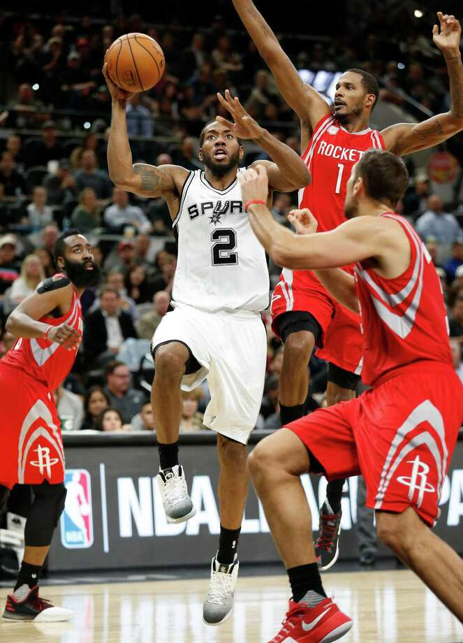 Spurs' Kawhi Leonard (02) attempts a shot while defended by Houston Rockets' Trevor Ariza (01) and Ryan Anderson (03) during their game at the AT&T Center on Wednesday, Nov. 9, 2016. (Kin Man Hui/San Antonio Express-News) Photo: Kin Man Hui, Staff / ©2016 San Antonio Express-News