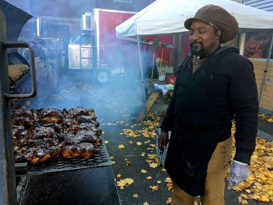 Ethan Aiken preparing jerk chicken at the corner of Park Avenue and Johnson Street in Bridgeport, Conn. on Friday, Nov. 11, 2016. Ethan Aiken and his son, Delroy use several large grills shifting dozens of chicken legs and racks of ribs over the open flames. The father and son have been grilling food in the Bridgeport lot for the past six months for sale on food trucks in New York and around Connecticut. Photo: Daniel Tepfer / Hearst Connecticut Media / Connecticut Post