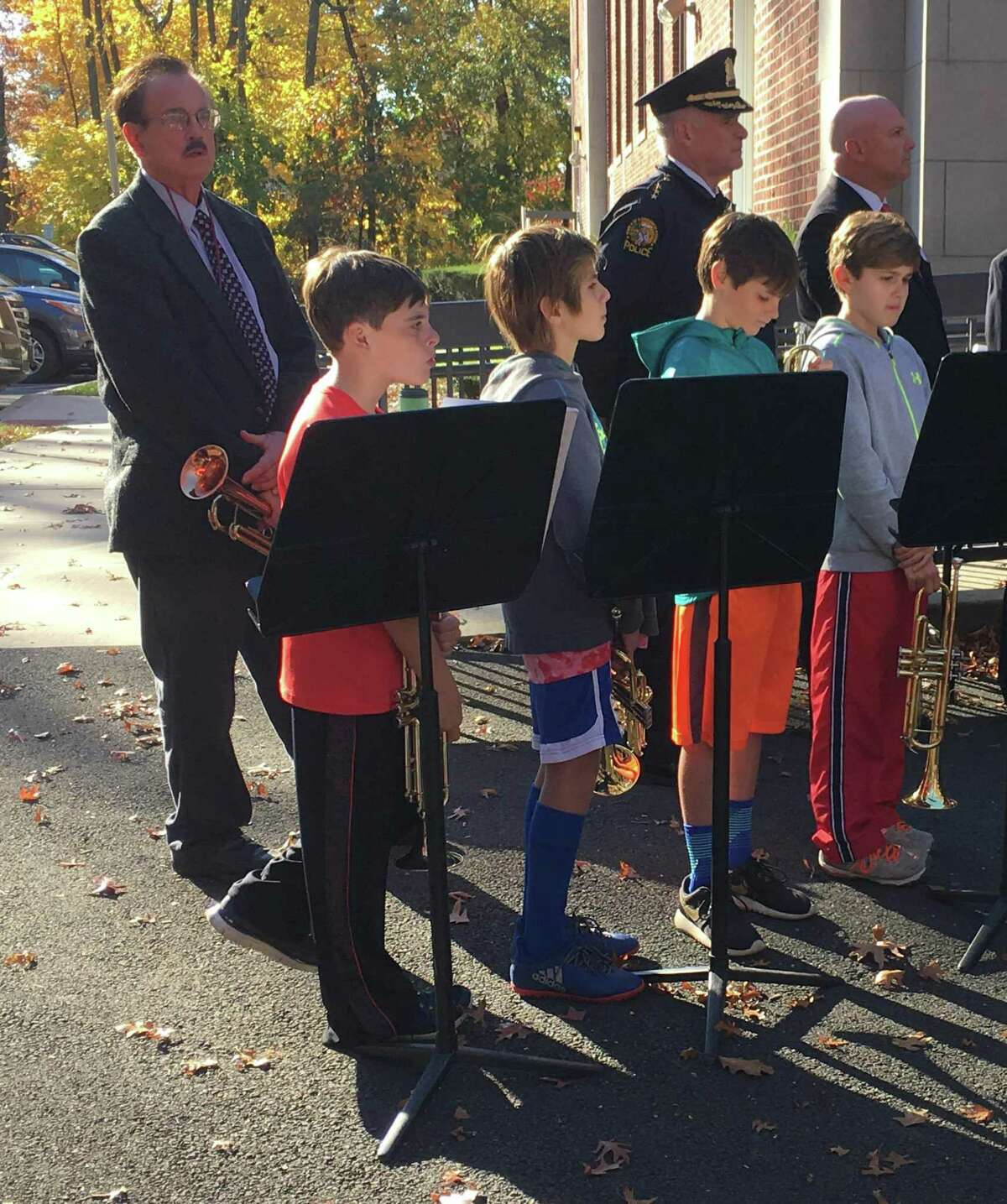 Four students stand at attention before playing Taps during the Veteran's Day ceremony at Riverside School Friday.