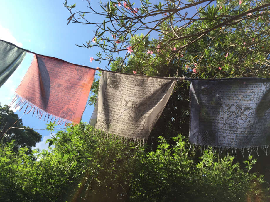 "Tibetan prayer flags blow in the breeze in Mary Hayslip's front yard. ¨Someone  dropped them off on my porch,"" said Hayslip. ""I don't know who: a mystery person."" Photo: Lucas Masllorens / Modest Digs"