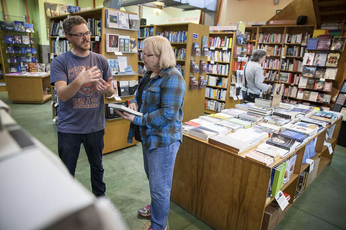 Brad Johnson, co-manager of Oakland's Diesel bookstore who is looking in to a community funded exchange with current owner to transfer and create the East Bay Booksellers, chat with customer Marls Contain during her visit from Chicago in Oakland, California, USA 11 Nov 2016. (Peter DaSilva/Special to The Chronicle)
