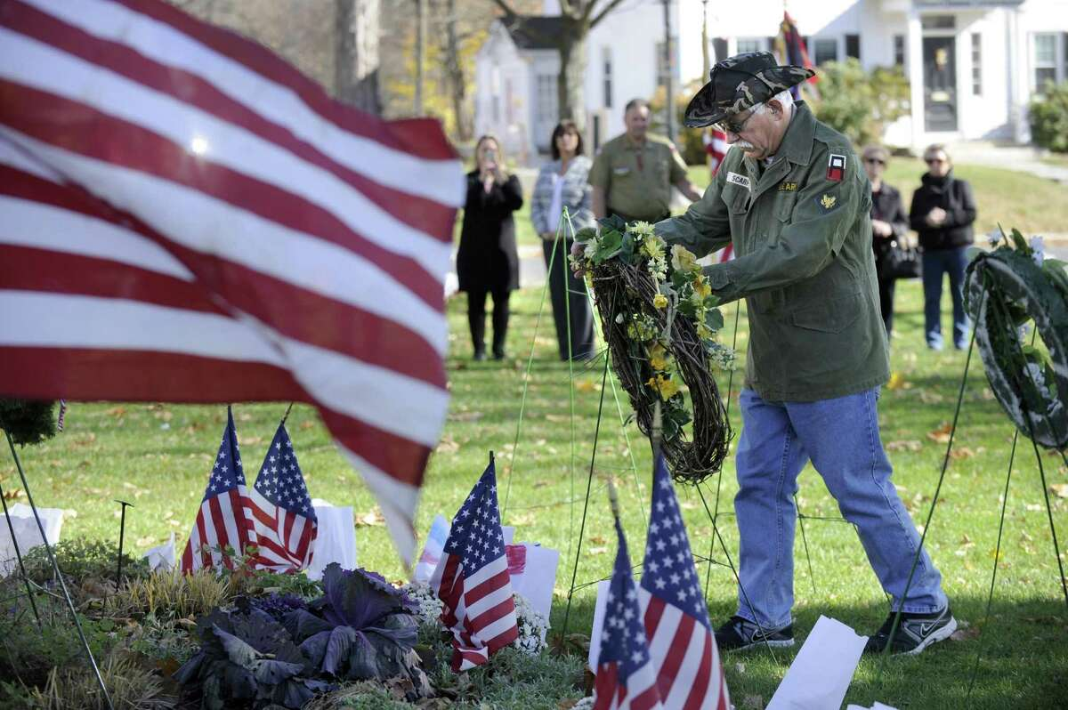 Tony Scarpone, a veteran who served during the Vietnam era, places a Freedom Wreath during New Milford's annual Veterans Day ceremony on the New Milford Green, Friday, Nov. 11, 2016
