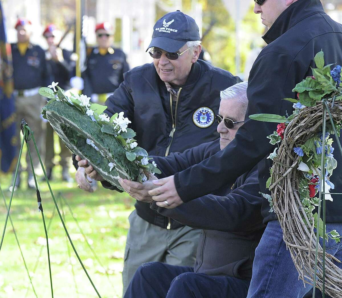 Dennis Brooks, center, places a Purity Wreath during New Milford annual Veterans Day ceremony on the New Milford Green, Friday, Nov. 11, 2016.