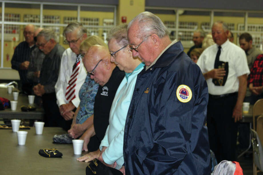 Bradley Massman/Huron Daily Tribune Veterans bow their heads during a moment of silence to pay honor to their fallen brothers and sisters Friday morning during a special breakfast at Harbor Beach Community Schools. The district holds a breakfast for local veterans each year as a way of saying thank you for serving our country.