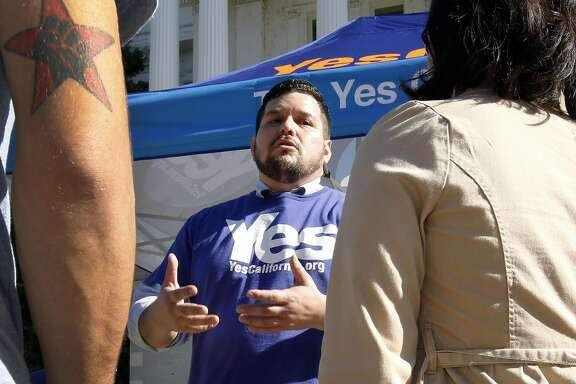 Marcus Ruiz Evans, center, of The Yes California Independence Campaign, talks to passersby about California succeeding from the United States and becoming its own nation, Wednesday, Nov. 9, 2016, in Sacramento, Calif., . Support for the proposal grew on social media following Tuesday's election of Republican Donald Trump.(AP Photo/Rich Pedroncelli)