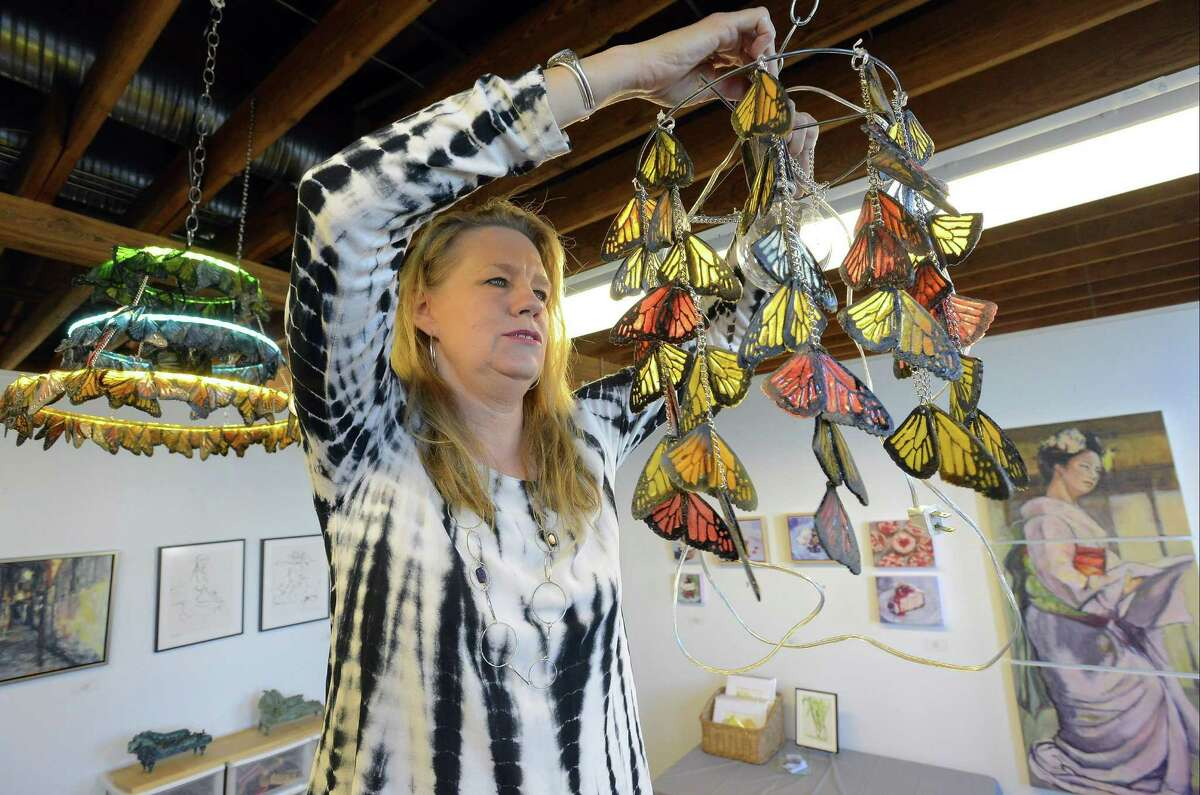 Lucienne Buckner of New Canaan, hangs a butterfly chandelier on Nov. 11, 2016, as she prepares her studio space at The Loft Artists Association for it's annual Open Studios. The LAA kicks off its annual Open Studios from 6 p.m. to 9 p.m. tonight (Friday), and continues Saturday and Sunday from noon to 5 p.m. Artists display their work and welcome the public into their personal studios at LAA. This is an annual event that is free to the public.