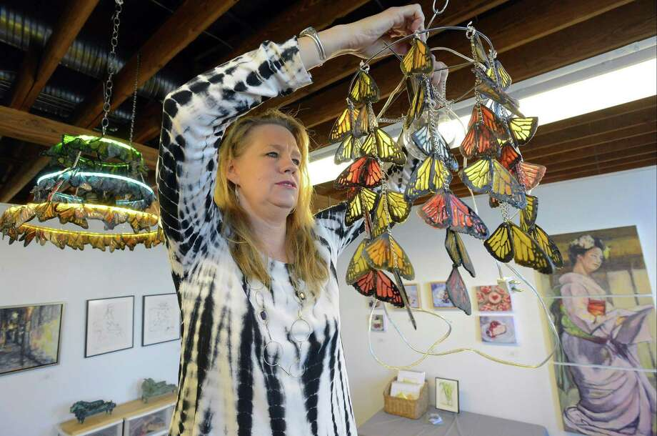 Lucienne Buckner of New Canaan, hangs a butterfly chandelier on Nov. 11, 2016, as she prepares her studio space at The Loft Artists Association for it's annual Open Studios. The LAA kicks off its annual Open Studios from 6 p.m. to 9 p.m. tonight (Friday), and continues Saturday and Sunday from noon to 5 p.m. Artists display their work and welcome the public into their personal studios at LAA. This is an annual event that is free to the public. Photo: Matthew Brown / Hearst Connecticut Media / Stamford Advocate
