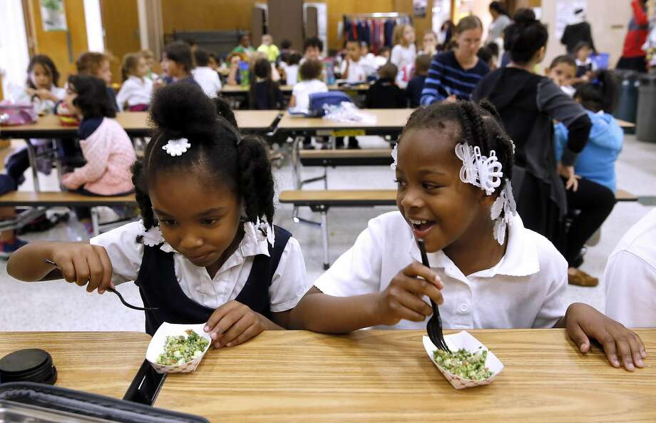 First-graders Miracle Tarrant (left) and Mi' Yani Moore approve of the tabbouleh in a Glenview Elementary taste test. Photo: Michael Macor, The Chronicle