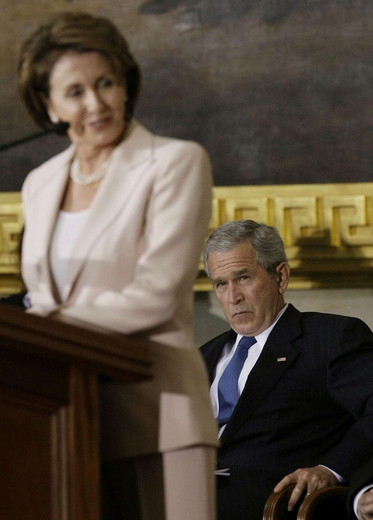 President Bush, right, listens as House Speaker Nancy Pelosi of Calif., left, speaks in the Capitol Rotunda on Capitol Hill in Washington, Tuesday, July 17, 2007, during a ceremony for Congressional Gold Medal recipient Norman Borlaug. (AP Photo/Pablo Martinez Monsivais)