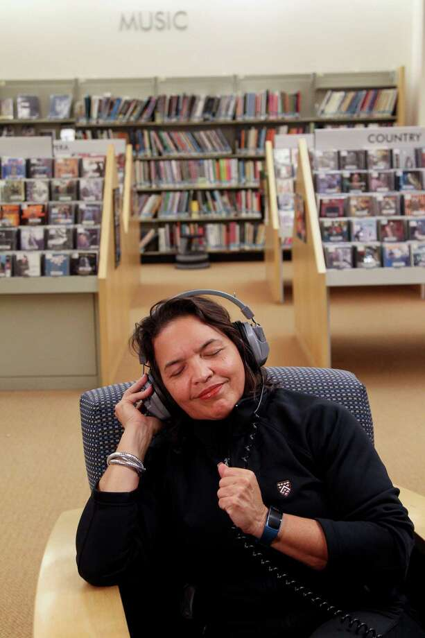 "Grooving to the sounds of one of her favorite groups, ""Chicago,"" at the Greenwich Public Library, Karen Chaplin listens to several CDs before borrowing some selections to listen to at home. Photo: Bradley E. Clift / For Hearst Media Connecticut / All images produced are owned by Bradley E. Clift  © 2016  Any use beyond Hearst  must have written permission from copyright ho"
