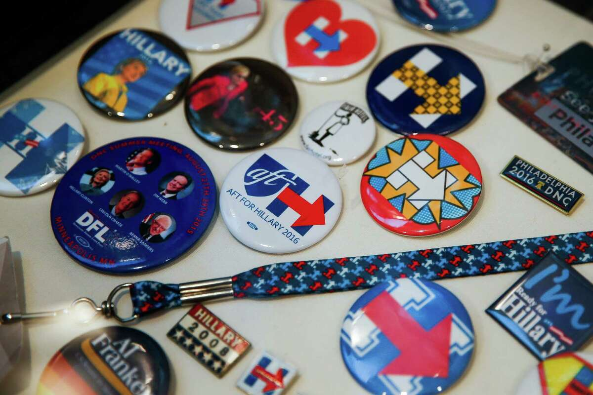 Campaign buttons sit in a glass case in Hillary Clinton supporter and founder of HRC Super Volunteers Kim Frederick's house Wednesday, Nov. 2, 2016 in Houston.